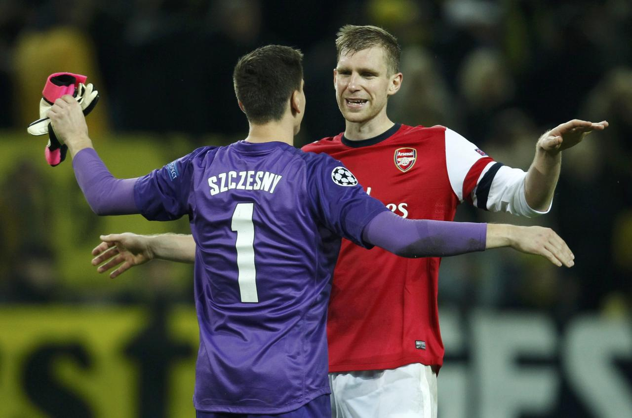 Arsenal'sSzczesny and Mertesacker celebrate after defeating Borussia Dortmund in Champions League soccer match in Dortmund