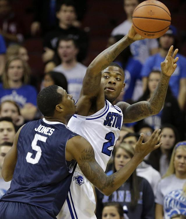 Seton Hall guard Fuquan Edwin (23) passes the ball over Monmouth guard Deon Jones (5) during the first half of an NCAA college basketball game in Newark, N.J., Monday, Nov. 18, 2013. (AP Photo/Mel Evans)
