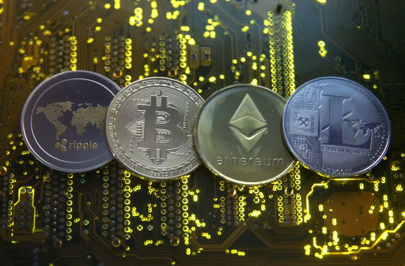 FILE PHOTO: Representations of the Ripple, bitcoin, etherum and Litecoin virtual currencies are seen on motherboard in this illustration picture