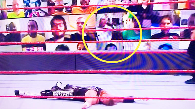 A WWE wrestler lying in the ring with virtual crowd members in the background., including a man appearing to wear a KKK garment.