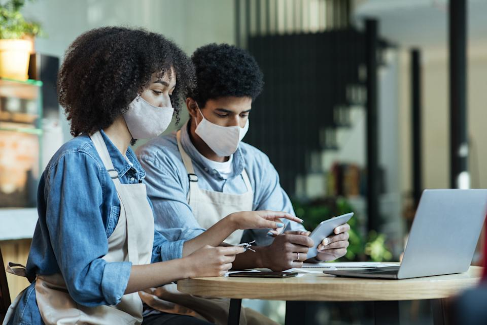 New normal and work of cafe during coronavirus and social networks. Small business owners, african american man and woman in protective masks and aprons use tablet and laptop in cafe interior