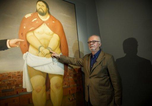 "Fernando Botero points at one of his paintings at the Museum of Antioquia in Medellin, Colombia, on April 1. Botero says his success comes from paintings that ""speak directly"" to the public and do ""not require explanation."""