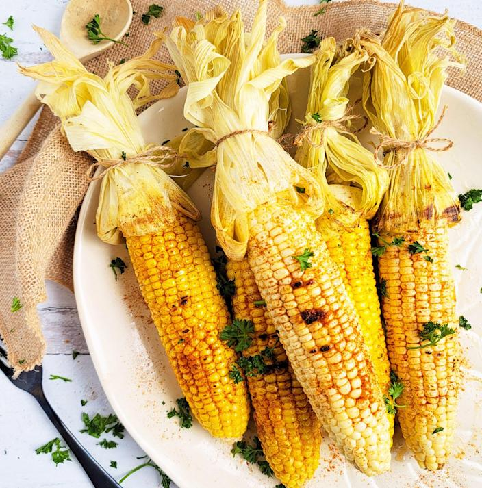 """<p>This grilled corn on the cob is a real summertime treat. It's basted with a spicy butter blend and grilled to perfection in about 20 minutes. This recipe is easily doubled to serve a larger gathering. This recipe is part of our <a href=""""https://www.eatingwell.com/article/7902588/juneteenth-family-cookout-menu/"""" rel=""""nofollow noopener"""" target=""""_blank"""" data-ylk=""""slk:Juneteenth Family Cookout Menu"""" class=""""link rapid-noclick-resp"""">Juneteenth Family Cookout Menu</a>.</p>"""