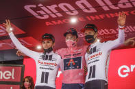 Britain's Tao Geoghegan Hart, center, winner of the Giro d'Italia cycling race, poses on the podium with second placed Australia's Jai Hindley, left, and third placed Wilco Kelderman, of The Netherlands, in Milan, Italy, Sunday, Oct. 25, 2020. (AP Photo/Luca Bruno)