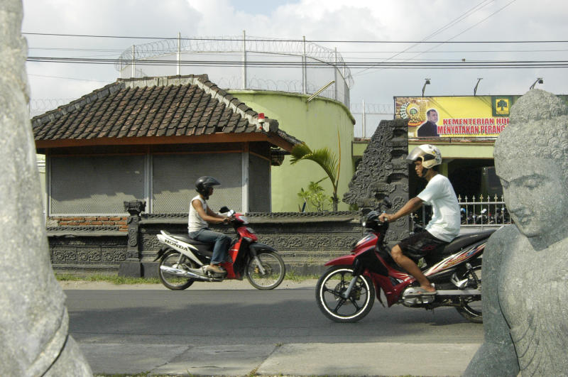 Two motorcyclists pass each other on a Bali road.
