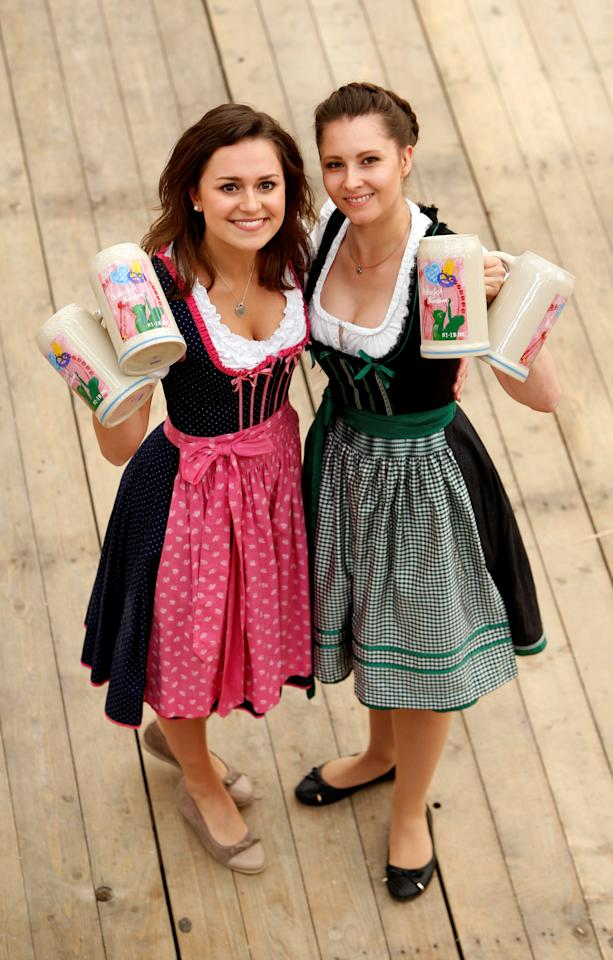 Model Laura and Maja wear traditional Bavarian costume as they hold the official Oktoberfest beer mugs during a presentation in Munich, Germany August 23, 2016. REUTERS/Michaela Rehle