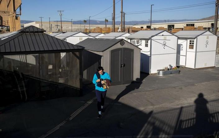 RIVERSIDE, CA - NOVEMBER 30, 2020: A resident of the the tiny home village walks to the common shower area on November 30, 2020 in Riverside, California. Los Angeles is embracing the idea of tiny homes to get homeless off the streets, but the buildings are sitting in storage.(Gina Ferazzi / Los Angeles Times)