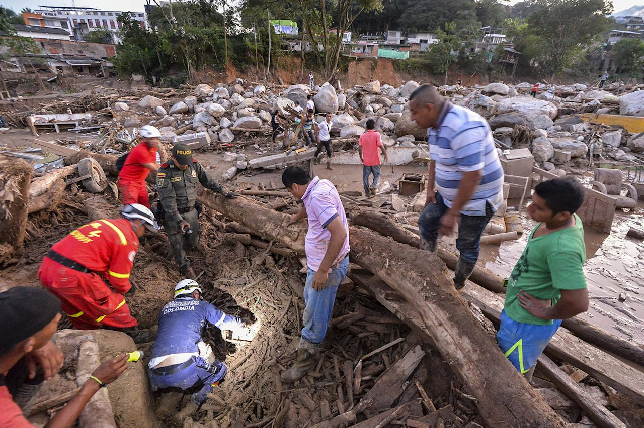 <p>Rescuers seek people among the rubble left by mudslides following heavy rains in Mocoa, Putumayo department, southern Colombia on April 1, 2017.<br /> (Luis Robayo/AFP/Getty Images) </p>
