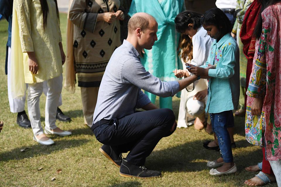LAHORE, PAKISTAN - OCTOBER 18: Prince William, Duke of Cambridge receives a bracelet on a visit to the SOS Village on October 18, 2019 in Lahore, Pakistan. (Photo by Neil Hall - Pool/Getty Images)