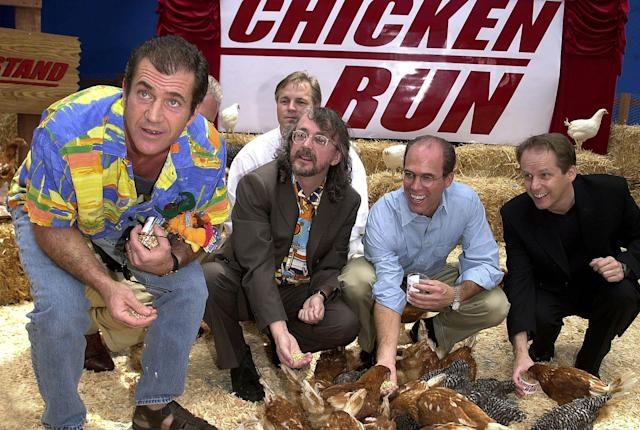 """Mel Gibson (L) feeds chickens at the premiere """"Chicken Run"""" with Peter Lord (2nd L) and Nick Park (R), and executive producer Jeffrey Katzenberg (2nd R), 2000. (LUCY NICHOLSON/AFP via Getty Images)"""