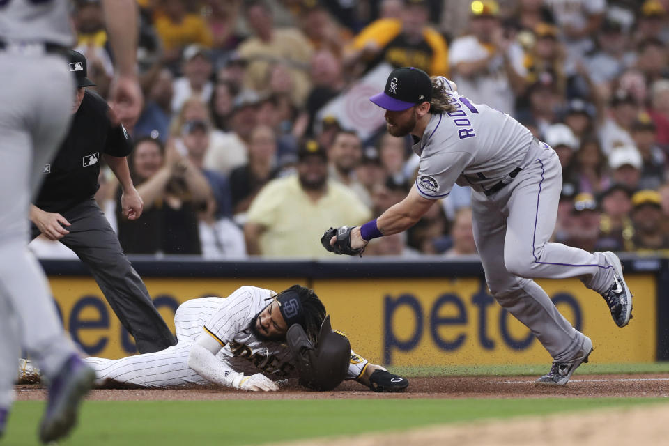 San Diego Padres' Fernando Tatis Jr. slides into third next to Colorado Rockies shortstop Brendan Rodgers during the first inning of a baseball game Friday, July 30, 2021, in San Diego. Tatis left the game. (AP Photo/Derrick Tuskan)
