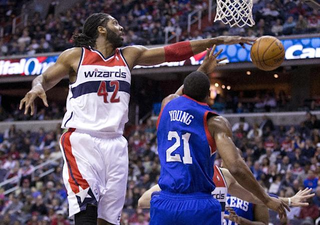 Washington Wizards power forward Nene (42), blocks a shot by Philadelphia 76ers forward Thaddeus Young (21) during the first half of an NBA basketball game on Monday, Jan. 20, 2014 in Washington. (AP Photo/ Evan Vucci)