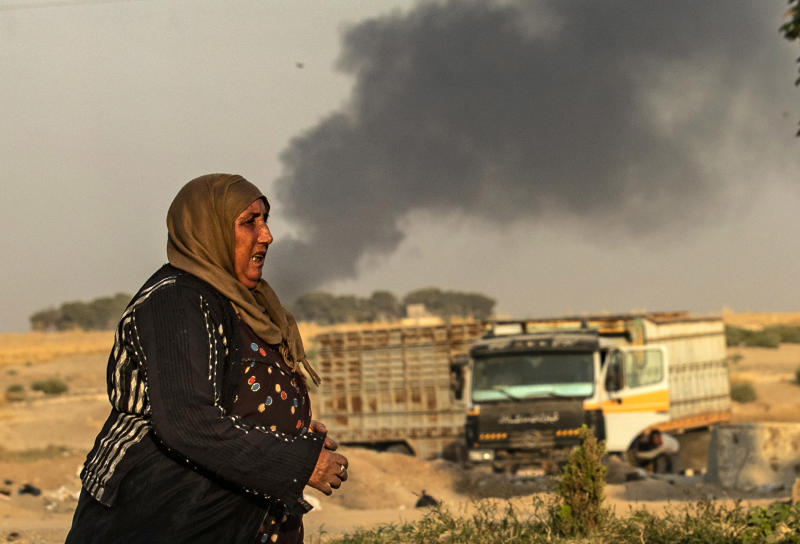 A woman walks as smoke billows following Turkish bombardment in Syria's northeastern town of Ras al-Ain in the Hasakeh province along the Turkish border on Oct. 9, 2019. (Photo: Delil Souleiman/AFP via Getty Images)