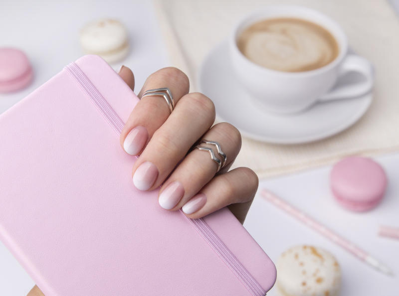 Beautiful manicured hand holding notepad at the office table. Ombre gradient nail design.