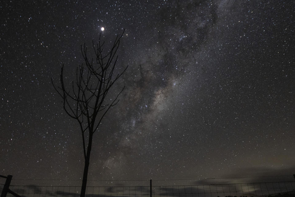 <p>RYLSTONE, AUSTRALIA - MAY 26: The supermoon is seen next to the milky way on May 26, 2021 in Rylstone, Australia. It is the first total lunar eclipse in more than two years, which coincides with a supermoon. A super moon is a name given to a full (or new) moon that occurs when the moon is in perigee - or closest to the earth - and it is the moon's proximity to earth that results in its brighter and bigger appearance. (Photo by Mark Evans/Getty Images)</p>