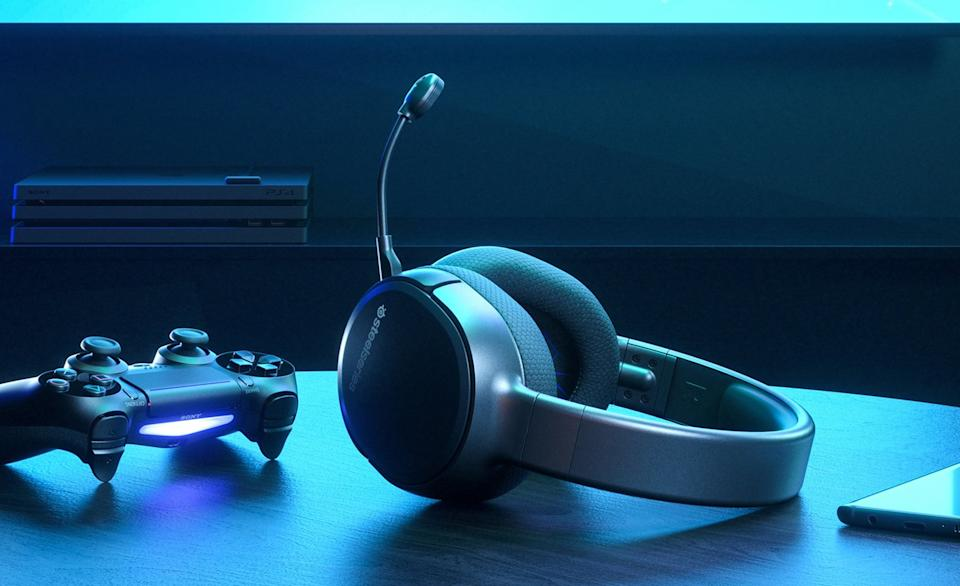 The SteelSeries Arctis 1 Wireless gaming headphones on a table bathed in bluish light from a monitor screen.