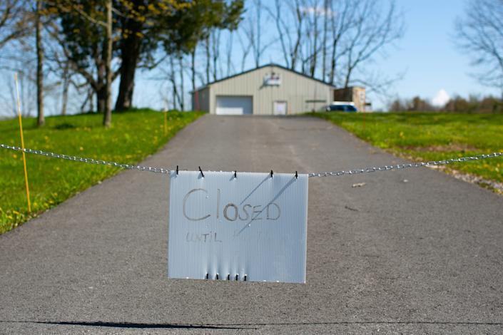 A closed sign hangs outside S&S Sales in Auburn, New York. The shop has been open, but by appointment only, during the stay-at-home order.