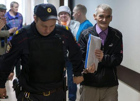 Historian Yuri Dmitriev is escorted by a police officer upon his arrival for a court hearing in Petrozavodsk