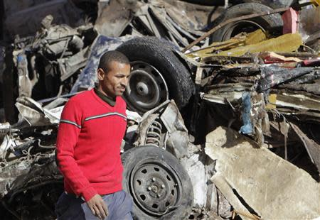 A man walks near a damaged vehicle after an explosion near a security building in Egypt's Nile Delta city of Mansoura
