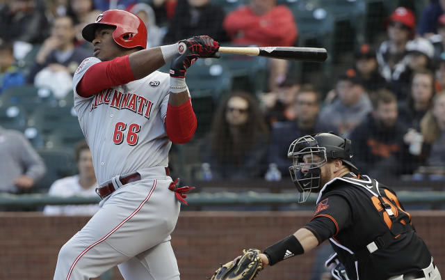 Cincinnati Reds' Yasiel Puig, left, hits a two-run home run in front of San Francisco Giants catcher Stephen Vogt during the first inning of a baseball game in San Francisco, Saturday, May 11, 2019. (AP Photo/Jeff Chiu)