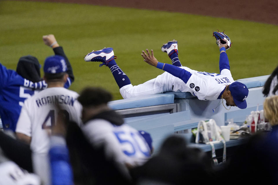 Los Angeles Dodgers right fielder Mookie Betts hangs on the wall as fans cheer after making a catch on a ball hit by Arizona Diamondbacks' Tim Locastro during the seventh inning of a baseball game Monday, May 17, 2021, in Los Angeles. (AP Photo/Mark J. Terrill)