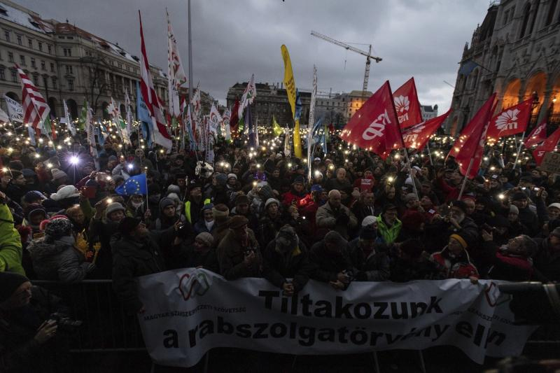 """Anti-government demonstrators carry a banner reading """"We protest against the slave bill"""" as they protest in front of the Parliament building at Kossuth square, donwtown Budapest, Hungary, Saturday, Jan. 5, 2019. The inscription refers to a bill raising the allowable overtime to 400 hours a year passed a few weeks ago by the Parliament. (Marton Monus/MTI via AP)"""