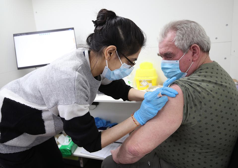 Pooja Patel vaccinates Stanley Piotrowski, 72, on Thursday, as a Tory lockdown sceptic called for all restrictions to be dropped as soon as the top nine priority groups of people receive a jab. (PA)