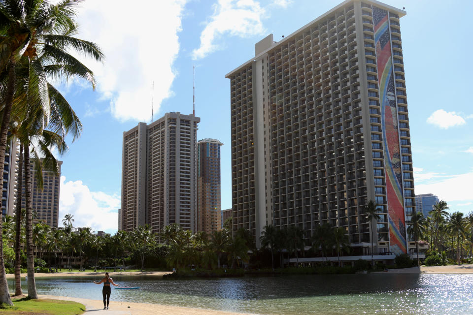 A woman exercises on a beach in front of a Hilton hotel in the Waikiki neighborhood of Honolulu, Friday, Oct. 2, 2020. After a summer marked by a surge of coronavirus cases in Hawaii, officials plan to reboot the tourism based economy later this month despite concerns about the state's pre-travel testing program. (AP Photo/Caleb Jones)