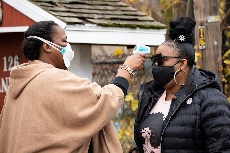 A volunteer checks temperatures before a training session as part of an outreach program to the Black community to increase vaccine trial participation in Rochester, New York, U.S., November 14, 2020. Picture taken November 14, 2020.  REUTERS/Lindsay DeDario