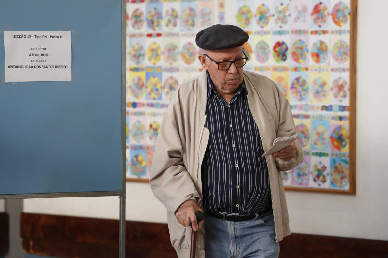 A man leaves a voting booth carrying his ballot paper at a polling station in Lisbon Sunday, Oct. 6, 2019. Portugal is holding a general election Sunday in which voters will choose members of the next Portuguese parliament. (AP Photo/Armando Franca)