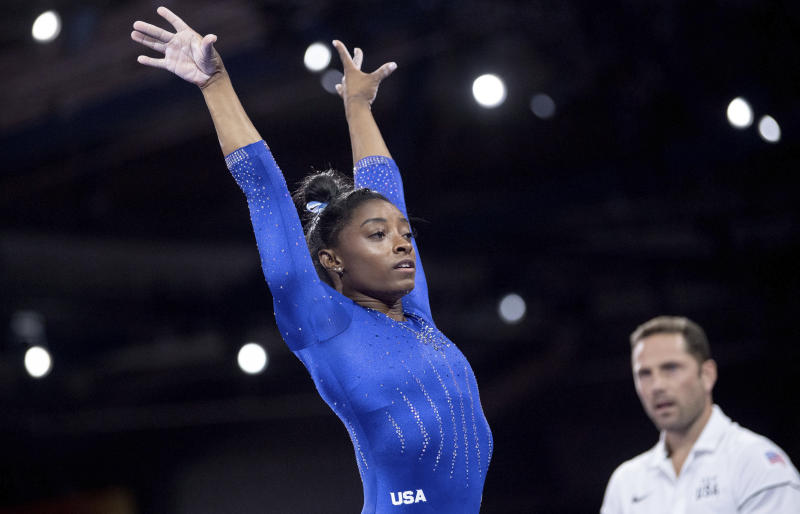 Simone Biles, of the United States, raises her arms after landing while competing in the Gymnastics World Championships in Stuttgart, Germany, Monday, Oct. 1, 2019. (Marijan Murat/dpa via AP)