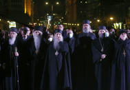 Priests watch a 23-meter-high, 70-ton bronze sculpture of the legendary founder of the Serbian state, Stefan Nemanja, during the unveiling ceremony in Belgrade, Serbia, Wednesday, Jan. 27, 2021. President Aleksandar Vucic's allies say the bronze sculpture of Stefan Nemanja will be a new landmark of the Serbian capital. Opponents think the monument is a megalomaniac and pricy token of Vucic's populist and autocratic rule that should be removed. (AP Photo/Darko Vojinovic)