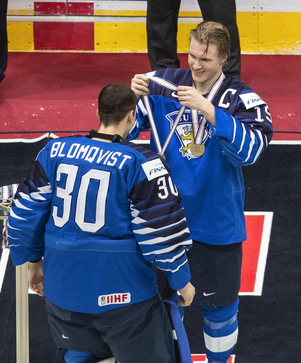 Finland goalie Joel Blomqvist (30) is presented the bronze medal by teammate Anton Lundell (15) after Finland defeated Russia in the third-place game of the IIHF World Junior Hockey Championship, Tuesday, Jan. 5, 2021, in Edmonton, Alberta. (Jason Franson/The Canadian Press via AP)