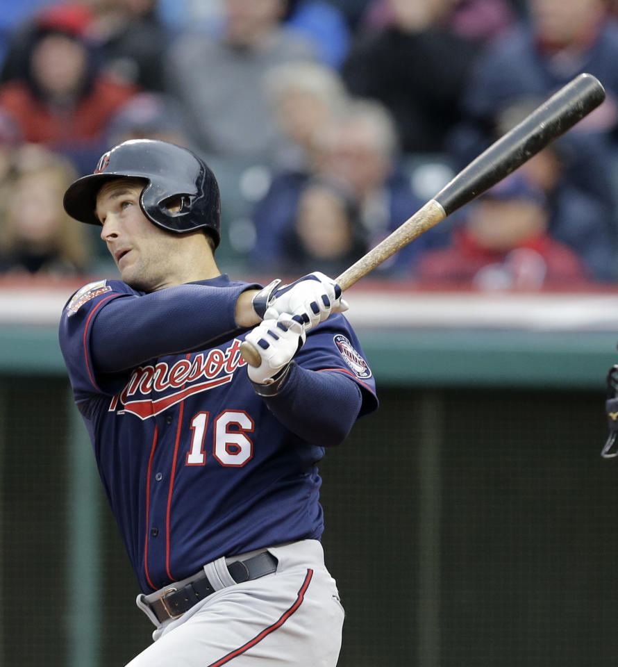 Minnesota Twins' Josh Willingham hits a sacrifice fly off Cleveland Indians starting pitcher Danny Salazar in the first inning of a baseball game, Friday, April 4, 2014, in Cleveland. Brian Dozier scored. (AP Photo/Mark Duncan)