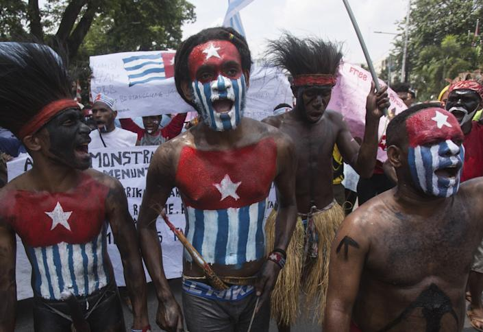 "Papuan students with their bodies and faces painted with the colors of the banned separatist Morning Star flag shout slogans during a rally in Medan, Indonesia, in 2019. <span class=""copyright"">(Binsar Bakkara / Associated Press)</span>"