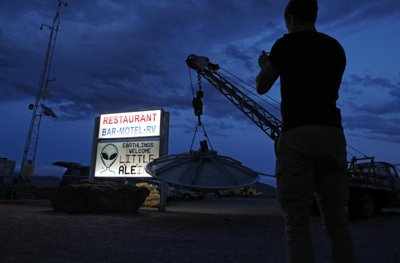 "A man takes a picture of a sign at the Little A'Le'Inn during an event inspired by the ""Storm Area 51"" internet hoax, Sept. 19, 2019, in Rachel, Nev. Hundreds have arrived in the desert after a Facebook post inviting people to ""see them aliens"" got widespread attention and gave rise to festivals this week. (Photo: John Locher/AP)"