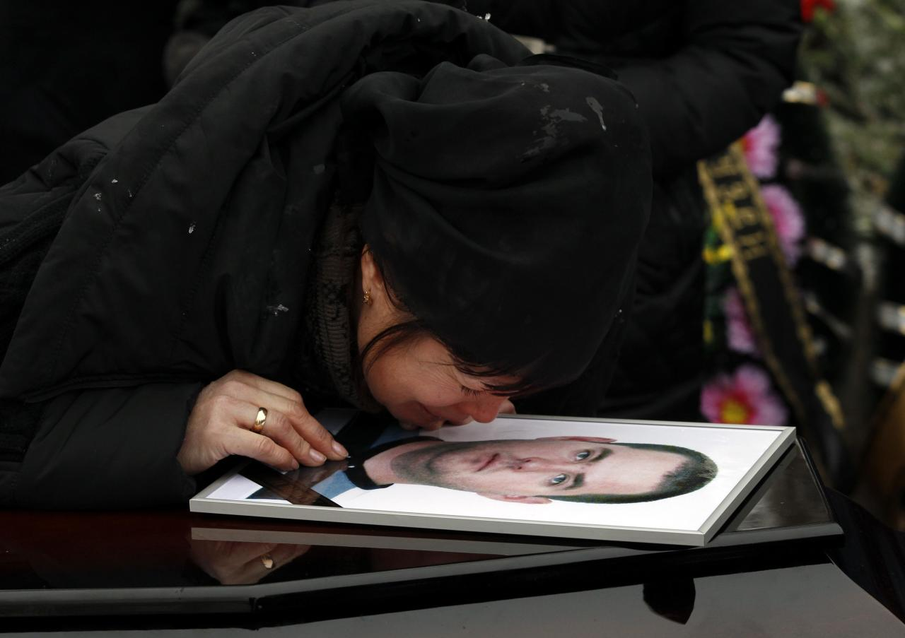 REFILE - CORRECTING BYLINE AT END OF CAPTION  A relative mourns during a funeral of a victim of an explosion in Volgograd December 31, 2013. Police detained dozens of people on Tuesday in sweeps through the Russian city of Volgograd after two deadly attacks in less than 24 hours that raised security fears ahead of the Winter Olympics. REUTERS/Vasily Fedosenko (RUSSIA - Tags: CIVIL UNREST CRIME LAW TRANSPORT)
