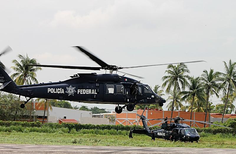 Two Black Hawk helicopters take off in Aquila, Michoacan state on July 24, 2013