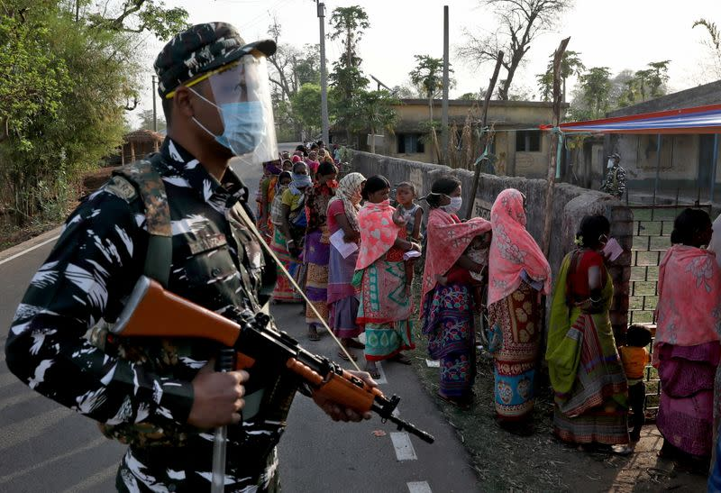 An armed policeman wearing a face shield stands guard as women wait in line to cast their votes outside a polling booth during the first phase of the West Bengal state election in Purulia
