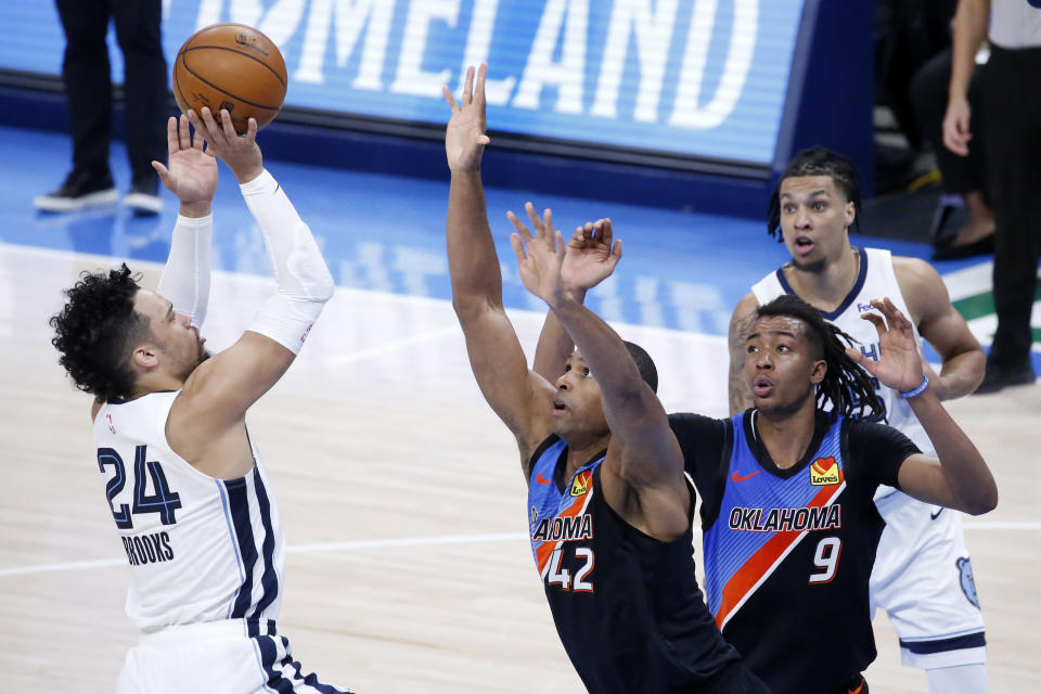 Memphis Grizzlies forward Dillon Brooks (24) takes a shot against Oklahoma City Thunder center Al Horford (42) and center Moses Brown (9) while Memphis Grizzlies forward Brandon Clarke (15) looks on during the first half of an NBA basketball game, Wednesday, March 24, 2021, in Oklahoma City. (AP Photo/Garett Fisbeck)