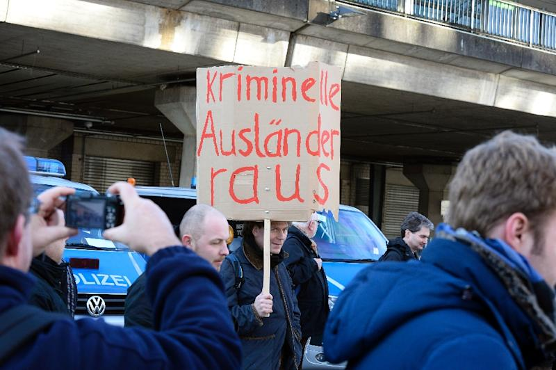 German far-right supporters hold a banner reading 'criminal forigners out' during a PEGIDA rally near Cologne's train station, on January 9, 2016 (AFP Photo/Roberto Pfeil)