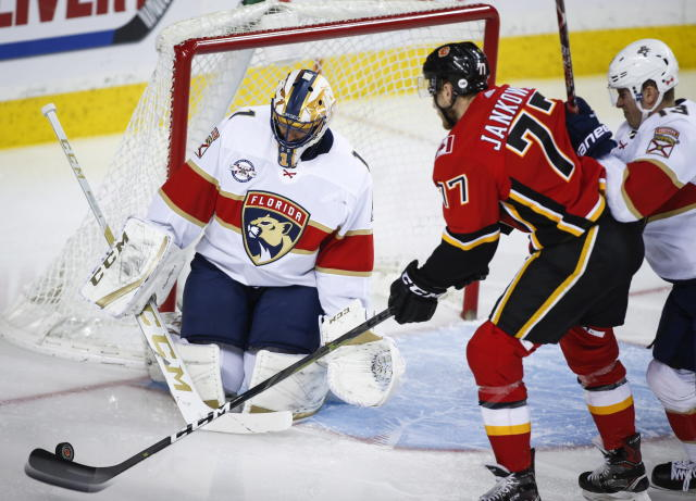 Florida Panthers goalie Roberto Luongo, left, blocks the net against Calgary Flames' Mark Jankowski during an NHL hockey game in Calgary, Alberta, Friday, Jan. 11, 2019. (Jeff McIntosh/The Canadian Press via AP)