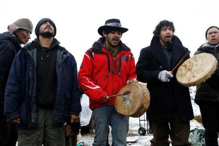 Members of the Cheyenne River Sioux Tribe and others sing as they prepare to evacuate the main opposition camp against the Dakota Access oil pipeline near Cannon Ball