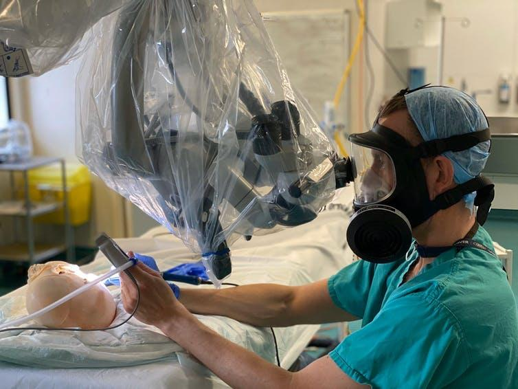 A surgeon in scrubs and a hairnet wears a respirator mask and looks down a microscope while simulating an operation on a skull.