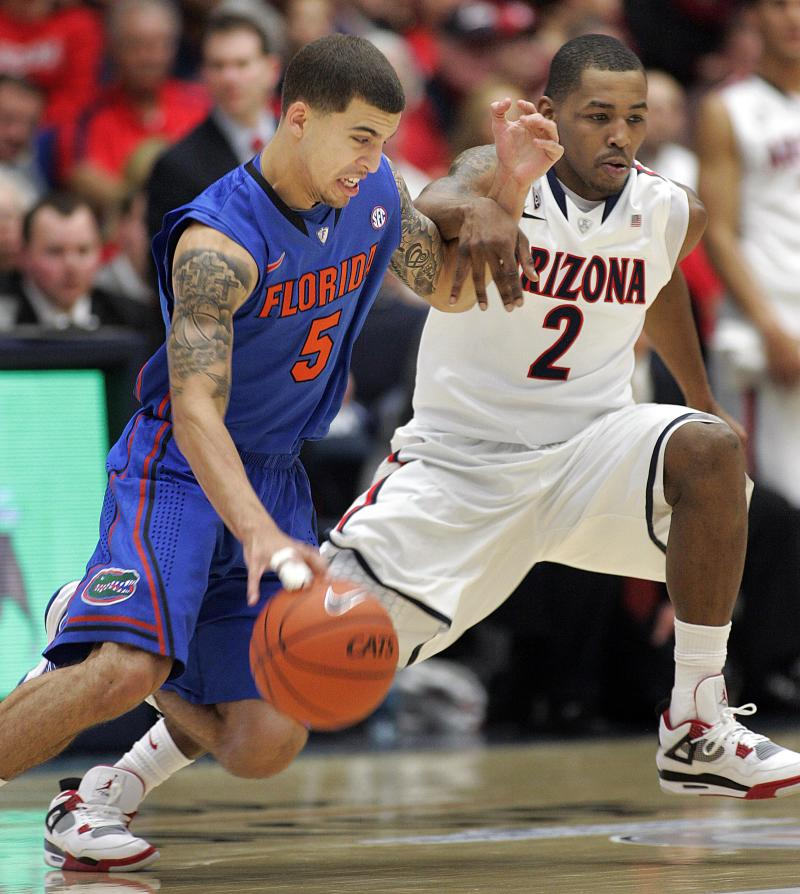 Florida's Scottie Wilbekin (5) drives pass the defense of Arizona's Mark Lyons (2) during the first half of an NCAA college basketball game  at McKale Center in Tucson, Ariz.,Saturday, Dec. 15, 2012. (AP Photo/John Miller)