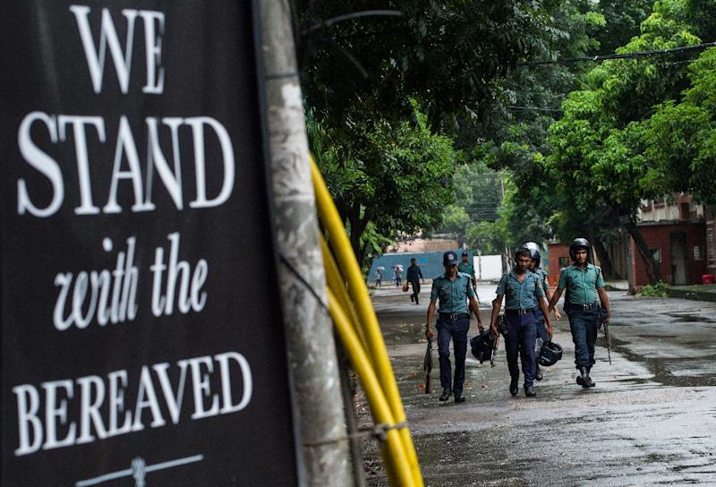 A sign of solidarity is placed near the restaurant where a bloody siege ended in the death of seventeen foreigners and five Bangladeshis, in Dhaka on July 5, 2016