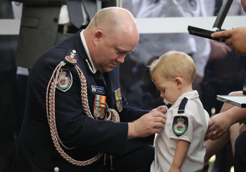 Mr Fitzsimmons is seen pinning Mr Keaton's bravery award on his young son Harvey's shirt. Source: RFS