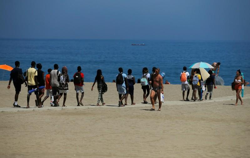 FILE PHOTO: People arrive at La Malagueta beach, as the summer's second heatwave hits Spain, in Malaga