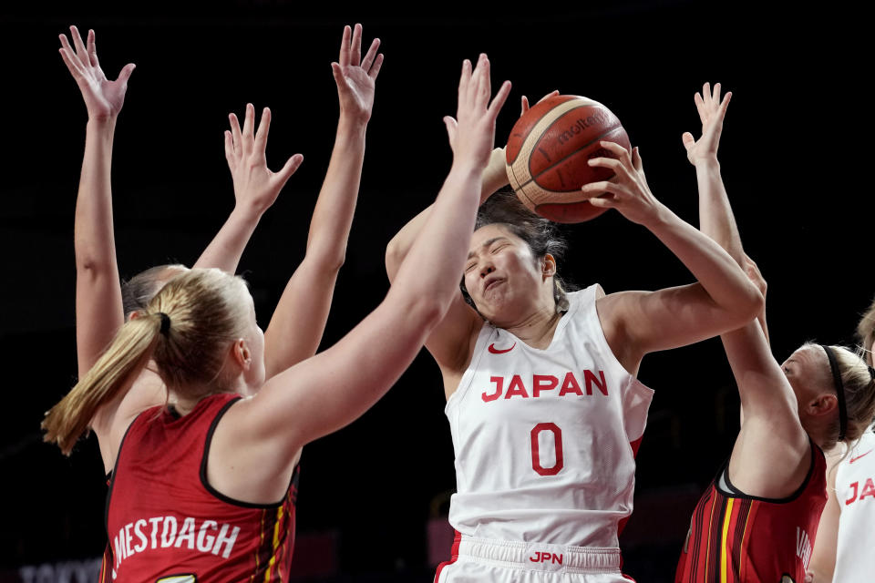 Japan's Evelyn Mawuli (30) grabs a rebound over Belgium's Hanne Mestdagh, left, and Belgium's Julie Vanloo , right, during a women's basketball quarterfinal game at the 2020 Summer Olympics, Wednesday, Aug. 4, 2021, in Saitama, Japan. (AP Photo/Eric Gay)