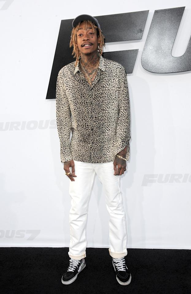 Looking perfectly preppy in white denim, a beat up baseball cap, and boat shoes, the rapper added some street flair with a cheetah print button down and neck tattoos.